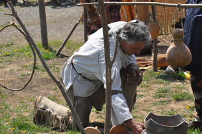 Lenape Lifeways demonstrates how to use an American Indian tool to a spectator.