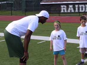 Jets QB Geno Smith listens to a question from a young camper