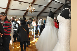 Wedding gowns and vendors line up within the Lake Mohawk Country Club Ballroom.
