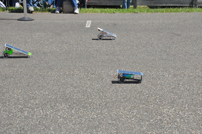 Solar cars speed along the track.