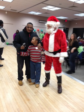 Santa at the LACD Holiday party with Leon Morton, a member of LACD, and his son Jared