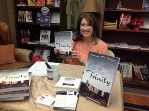 NJ Author proudly holds up her novel Trinity