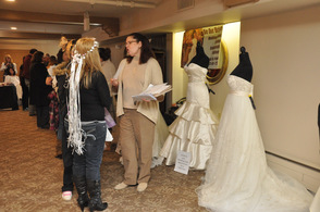 Brides talk bridal gowns with one of the vendors.