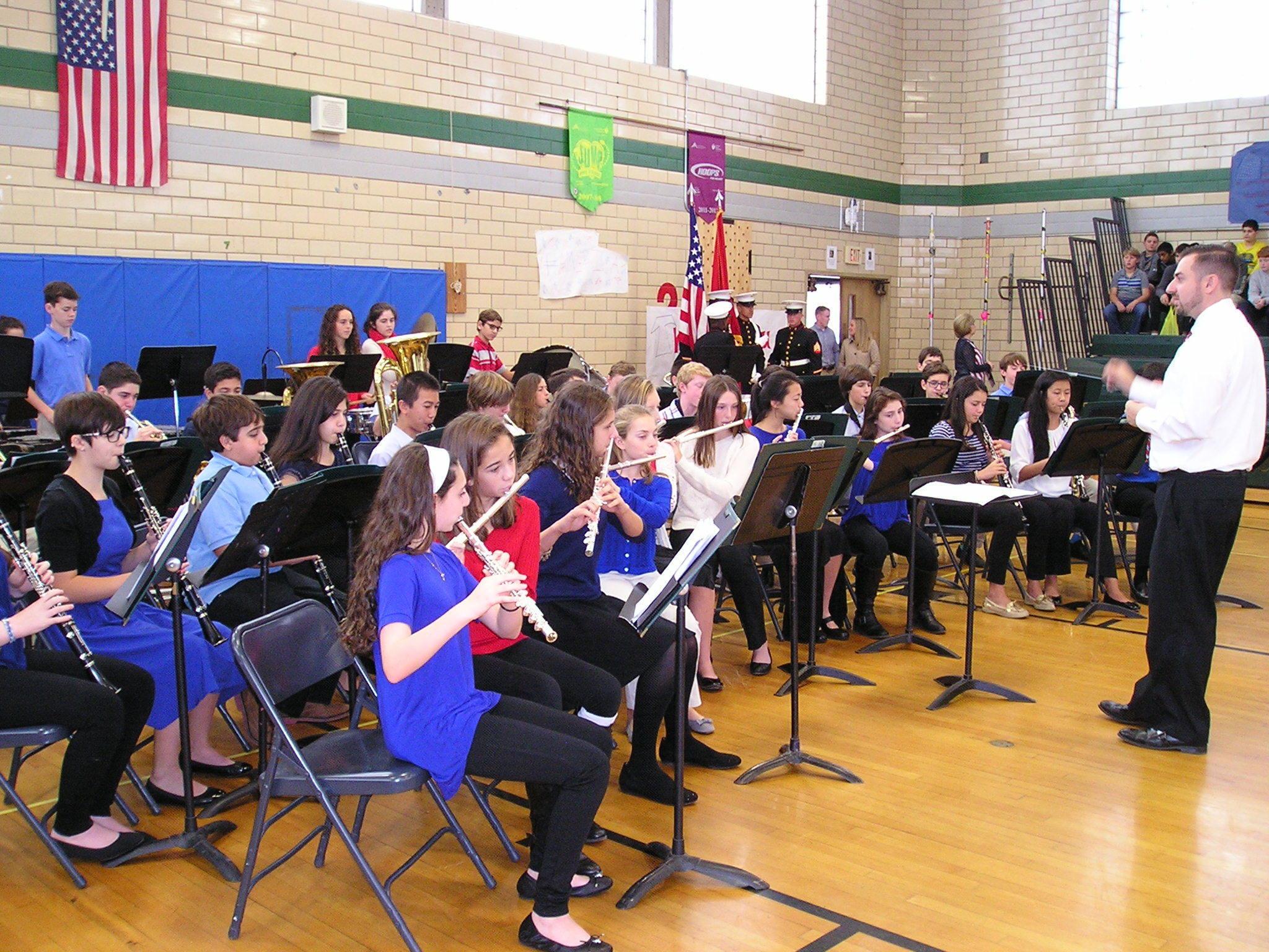 68676c018d6efaaca9aa_EIS_band_teacher_John_Scozarro_conducts_Concert_Band_at_Vets_Assembly.JPG