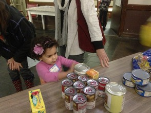 Preschooler, Luzita Avila of Maplewood, helps sort food and has a hands-on lesson about repairing the world when she visited the Interfaith Food Pantry of the Oranges with her preschool class at Temple Sharey Tefilo-Israel of South Orange.