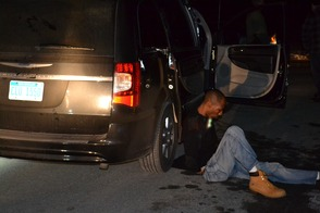 """""""James Bond Gang"""" members (l-r) Leevan Lawrence and Jerry Montgomery sit handcuffed on Radcliff Drive after they were removed from the their vehicle at gunpoint by Sparta Police after they committed a burglary on Greenfield Hill."""