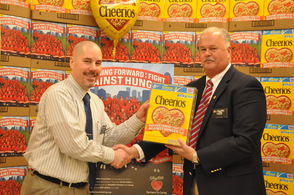 Store manager John DeCarlo, receives a special Cheerios Box from general manager, Hank Ramberger.
