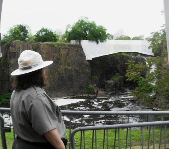 f547527eb5c917ca38f9_Ap_art_walk_forest_Ranger_looks_at_falls.jpg