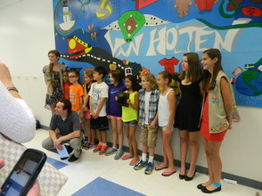 Students pose in front of the mural.