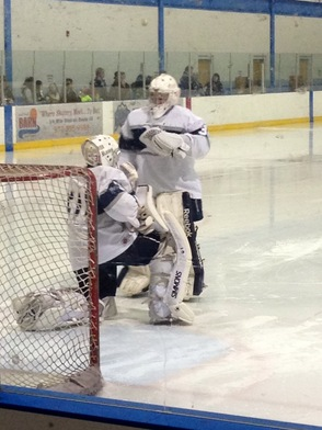 Garret Stenberg helps Andrew Holowko Prepare for the Second Period