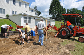 A segment of the crew digs in the dirt, while Andover Township Mayor Michael Lensak donated his time in the backhoe.