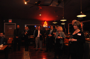 Chamber members gather around and listen intently to Tammie Horsfield speaking.