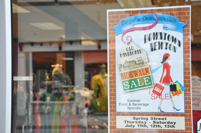 Sign about the sidewalk sale hangs in the window of PB&J Stores.