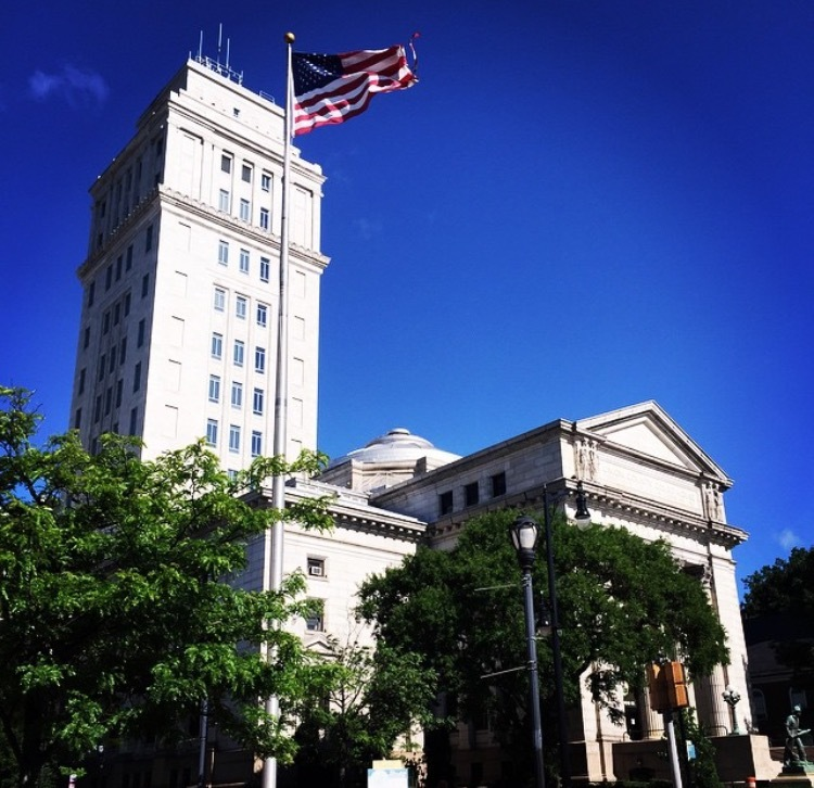 1c89b9e28b050b34327c_County_Courthouse_with_flag_resized__John_Roman_.PNG