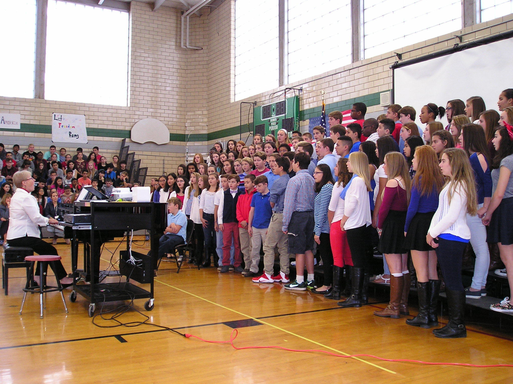 3479cb706637f9e4e58c_EIS_Vocal_teacher_leads_8th_Grade_Chorus_during_Vets_Assembly.JPG