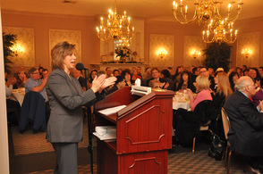 Sussex County Chamber of Commerce President Tammie Horsfield, leads breakfast attendees in applause.