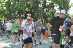 Runners coast by spectators during the 5K.