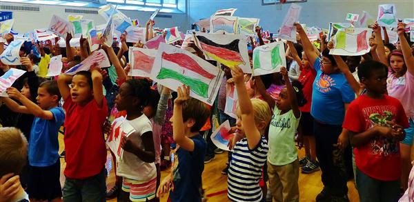 7482e110996378e39b3b_Students_wave_their_flags_at_the_assembly..jpg