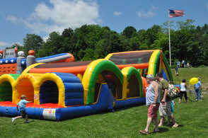 An excited child runs towards the bounce house.