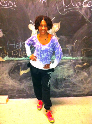 Dionne Scott in front of a mural inside of Blue Life Karate