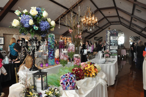 A burst of colorful bouquets and floral centerpieces await the brides in the Lake Mohawk Country Club ballroom.