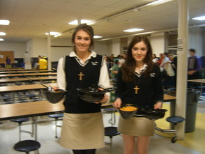 Tori Litterio on the left and Dominique Zaugg on the right, Leadership Council Coordinators and Servers, bringing empty bowls back down to the cafeteria from the parents eating upstairs.