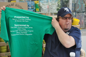 Michael Furrey of Agra Environmental & Laboratory Services holds up the t-shirt listing sponsors.