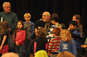 Peter Yarrow plays guitar with audience members around him.