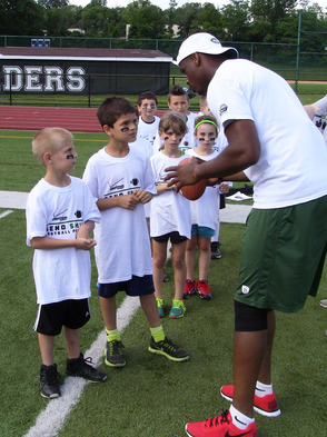 Geno Smith gives football instruction to attentive young players