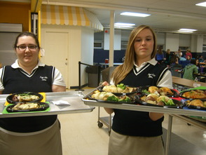 Christina Mendralla (left) and Hayley Kerrison (right), both members of Leadership Council and servers for Dinner Theater Night, are receiving their food to serve to parents.