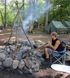 Crew Vice President Chris Rozek cooks part of a meal over a fire using a lashed tripod.