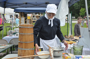 A woman in costume shows how butter is churned.