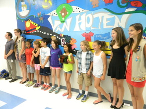 Students pose in front of the mural