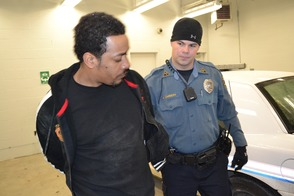 Officer Adam Carbery escorts Leevan Lawrence into the Sparta Police Department's cellblock.