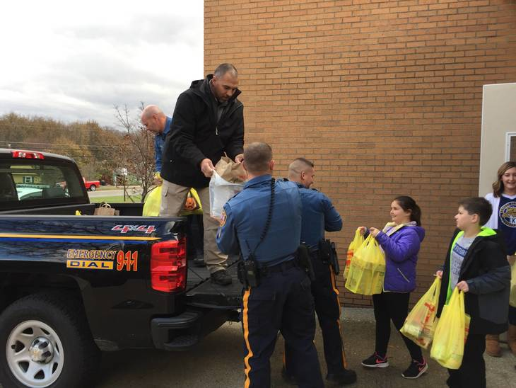 3636da43b5ba415d22d4_Early_Act_Students_load_up_the_police_truck_2.JPG