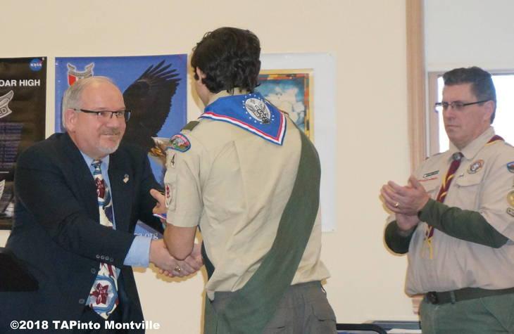 65f8fc1b2204c31f986d_a_Former_Mayor_Jim_Sandham_shakes_Michael_Manetta_s_hand_as_Scoutmaster_Patrick_Phalen_looks_on__2018_TAPinto_Montville.JPG