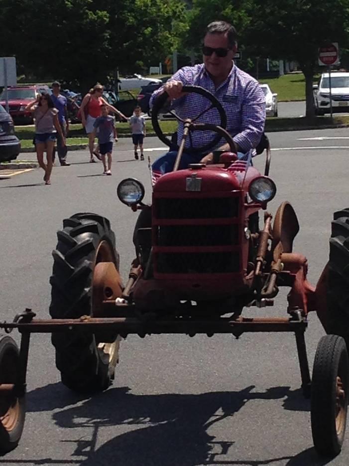 76990aaf498ae2b19a9c_Mayor_Riding_Tractor.jpg