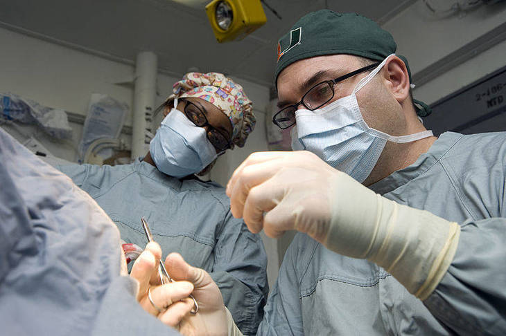 9a7ccb349f14fb7ff949_800px-US_Navy_120120-N-JN664-004_Lt._Cmdr._Howard_Pryor__a_Navy_doctor__stitches_an_incision_while_Hospital_Corpsman_3rd_Class_Destiny_Dansby_observes_in.jpg
