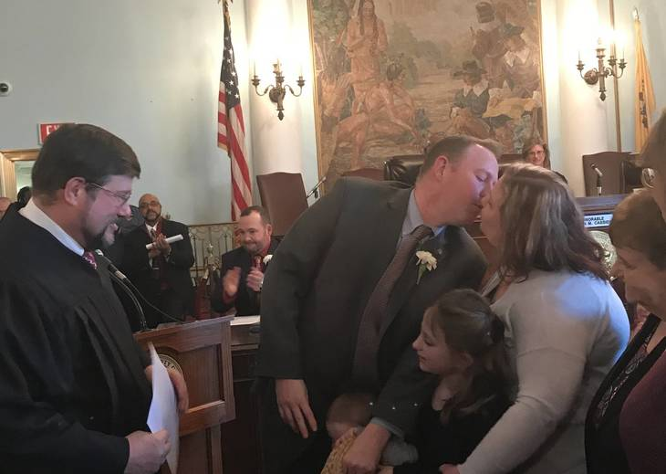 9af380d2d7dc7f90c322_d96be907da4961b35a03_Freeholder_Hudak_kisses_wife_after_being_sworn_in_by_his_Father.jpg