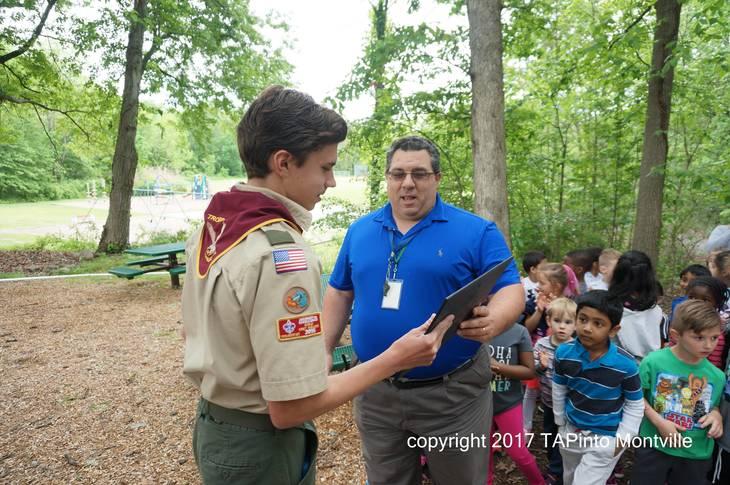 ac01713e557f1ecd0f27_a_Principal_Dominic_Esposito_hands_Life_Scout_Conner_Phalen_a_certificate_water.jpg
