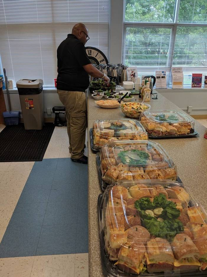 c9e810ab8ea503987fc5_SrProgram_Coordinator_Amefika_Gray_setting_up_lunch.jpg