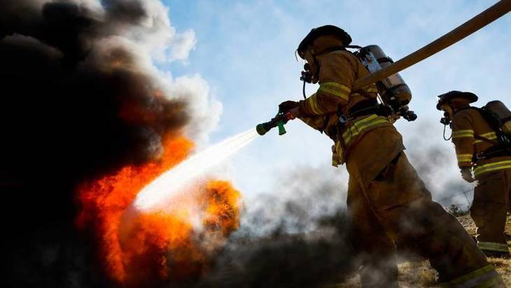 ffc38c876eb37a84e767_firefighter-carrying-hose.jpg