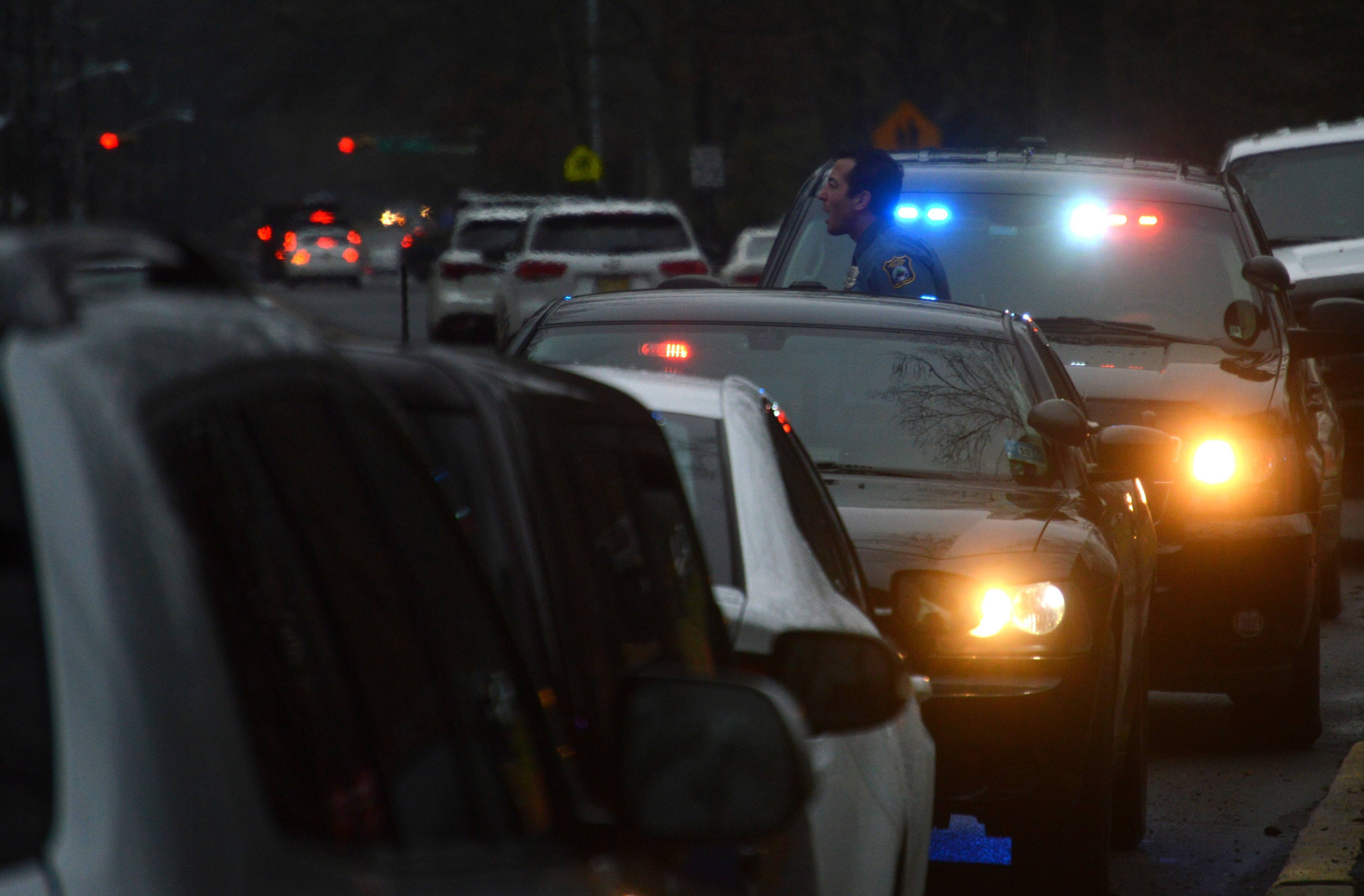d73bfe356b7fc55ac2d3_bd67073459ac717842b1_Police_officer_answers_questions_from_people_attempting_to_enter_JCC_parking_lot..JPG