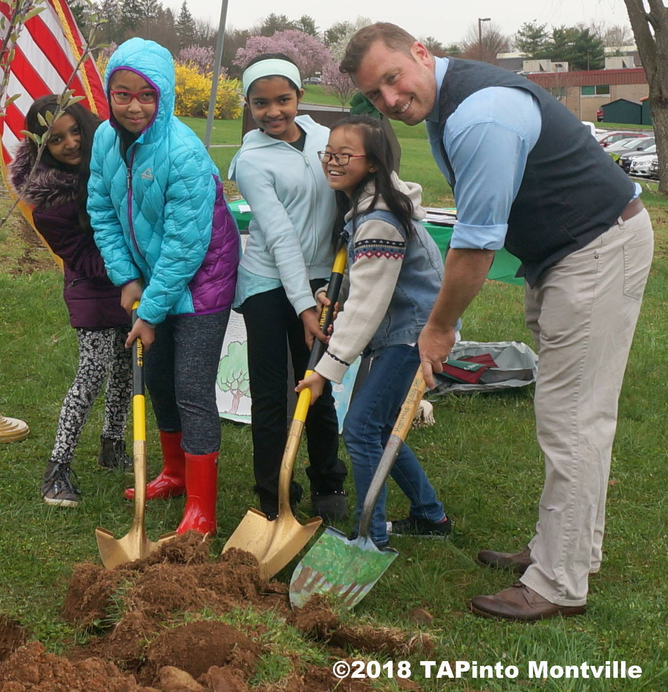 fc17a93334b8f190e4f6_a_The_poster_contest_winners_and_honoree_Paul_Rolfe_get_ready_to_plant_the_apple_tree__2018_TAPinto_Montville____1..JPG