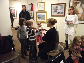 Kids line up to 'pet' the violin with NJYS student Johanna Nowick
