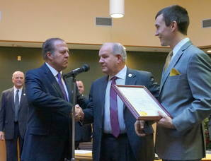 Freeholder Tom Mastrangelo shakes Mayor Jim Sandham's hand as Freeholder Hank Lyon holds a congratulatory resolution from the county
