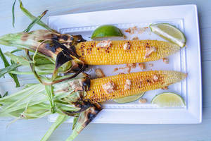 Carousel image a1d06c21c538648a763c behind the plates chili butter corn on the cob with lime