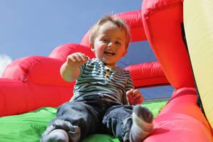 Carousel image b10aeb0a968401fba542 boy on inflatable slide