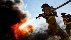 Carousel_image_ffc38c876eb37a84e767_firefighter-carrying-hose
