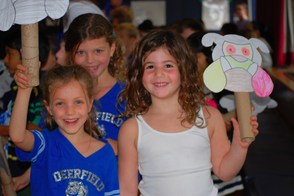 First graders Jacquelyn Murnick (left), Addison Lebersfeld (back) and Sydney Levin show their school spirit at Deerfield Elementary School's Schoolebration on September 27, 2013.